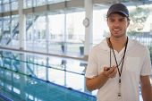 Swimming coach standing by the pool smiling at camera at the leisure center