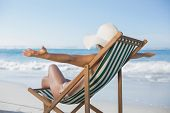 Woman relaxing in deck chair with arms outstretched on a sunny day