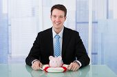 Businessman Protecting Piggybank With Lifebelt