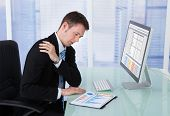 Businessman Having Shoulder Pain At Computer Desk