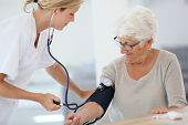 Doctor checking elderly woman's blood pressure
