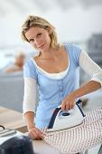 Housekeeper at home ironing clothes for old woman