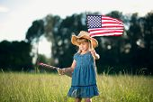 Little girl with American flag and toy gun.