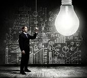 Businessman switching on light bulb with business sketches at background