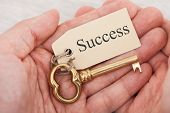 Man Holding Key With Success Tag