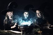 Three little Halloween witches reading spell above pot