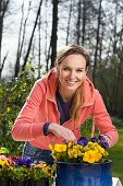 Smiling Woman Planting Pansy Flowers