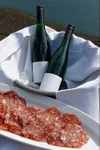 Two bottles on whine and salami served outdoors