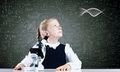 Cute school girl with microscope against blackboard with formulas