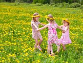 Three little girls wearing dandelion wreath enjoying a summer day outdoors