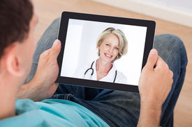 stock photo of chat  - Man having video chat with female doctor on digital tablet at home - JPG