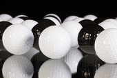 White And Black Golf Balls On The Glass Table