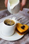 Someone Adds Milk To Black Coffee