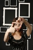 Woman framing her eyes with fingers