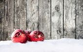 Christmas decorative red balls on snow with wooden planks as background