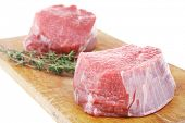red fresh fillet chops : two raw beef fillet chops on wooden board with small thyme twig ready to prepare . isolated over white background