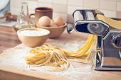 picture of pasta  - fresh pasta and pasta machine on kitchen table - JPG