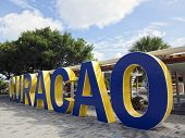 Word Curacao written in blue and yellow painted concrete letters at Queen Wilhelmina Park, Willemstad, Curacao