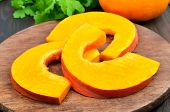 Raw Pumpkin Slices On Cutting Board