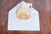 Open envelope with euro banknotes on table