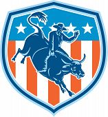 image of bull-riding  - Illustration of rodeo cowboy riding bucking bull set inside shield crest with american stars and stripes flag in the background done in retro style - JPG