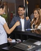 Guests receiving key card from receptionist at hotel.