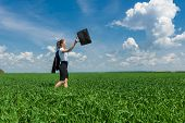 girl with a briefcase walking on green grass field