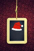 Hanged old slate board with Christmas cap chalk drawing