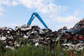 Scrap yard with crushed cars and blue sky