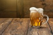 Light beer in mug on wooden background
