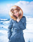 Portrait of beautiful woman on cold weather outdoors, wearing stylish casual blue coat with furry hood, wintertime fashion, winter holidays concept