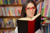 Young Woman with Glasses Reading Near Bookshelf