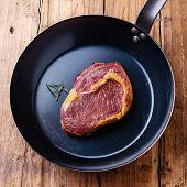 Raw Meat Ribeye Steak On Cast Frying Pan On Wooden Background