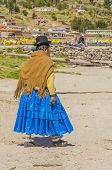 COPACABANA, BOLIVIA, MAY 7, 2014: Local woman in traditional attire walks down the street