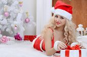 oung beauty smiling santa woman near the Christmas tree