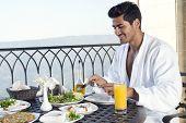 handsome man wearing bathrobe, and having breakfast outdoor