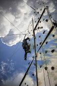 man climbing a rock climbing wall up to the sky