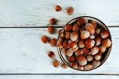 Hazelnuts in bowl on wooden background