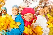 Happy friends with beautiful leaves bunches