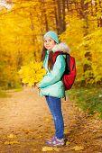 Schoolgirl with bunch of yellow maple leaves