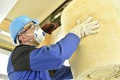 Man holding glasswool rolls in new built house