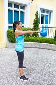 Beautiful sporty hispanic woman in blue training with kettlebell doing the swing routine