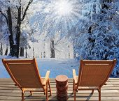 Christmas in the forest. Trees covered with snow, shine to the December winter sun. Comfortable wooden chairs and a small round table invite tourists to relax and enjoy the winter wonderland