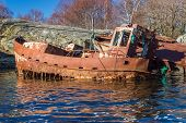 stock photo of shipwreck  - Back and side of very rusty old shipwrecks close to land and rocks - JPG