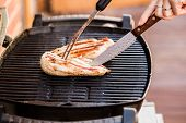 picture of  breasts  - Prepering of grilled chicken breast fillets cutted by knife on BBQ - JPG