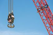 stock photo of hook  - Red crane boom with steel hook against blue sky - JPG