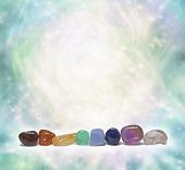 stock photo of ethereal  - A row of chakra colored tumbled semi precious gemstones on a swirling sparkling ethereal pastel colored background with plenty of copy space - JPG