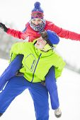 image of piggyback ride  - Happy young man giving piggyback ride to woman in snow - JPG