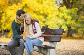 image of shy woman  - Passionate young man hugging shy woman on park bench during autumn - JPG