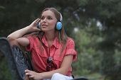 picture of muse  - Beautiful young woman listening musing through headphones in park - JPG